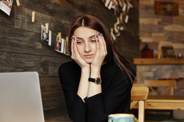 Gestresste junge kaukasische freiberuflerin, die ihr gesicht auf ihren händen ruht und mit gelangweiltem gesichtsausdruck auf den laptopbildschirm vor ihr schaut und sich müde fühlt, während sie aus der ferne im café arbeitet. menschen und lebensstil