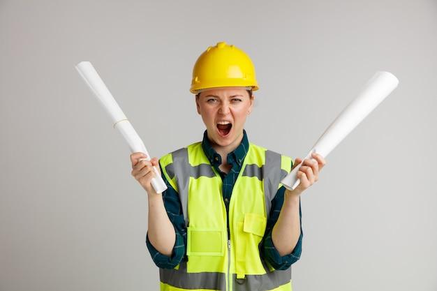 Gestresste junge weibliche bauarbeiterin, die schutzhelm und sicherheitsweste hält, die schreiende papiere hält