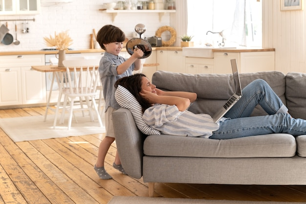 Gestresste mutter deckt ohr von lautem sohn ab, der von kinderfrau müde ist, die mit geschlossenen augen auf dem sofa liegt