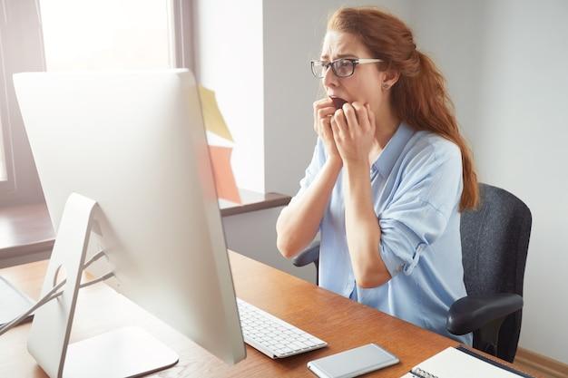 Gestresste schockierte geschäftsfrau, die am tisch vor dem computer sitzt