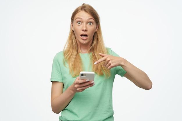 Gestresste und schockierte junge frau mit einem blonden langen haar zeigt mit einem finger in ihr telefon, mit weit geöffneten augen und verwirrtem gesichtsausdruck