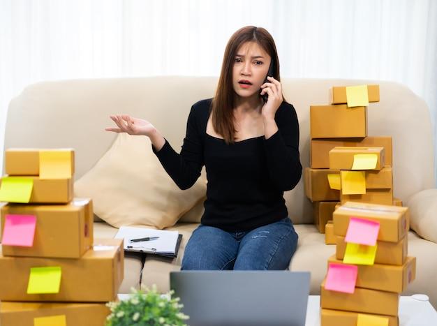 Gestresste unternehmerin, die problem auf einem smartphone spricht, um produkt online zu hause büro zu verkaufen
