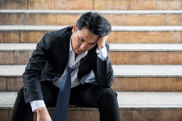 Gestresster asiatischer geschäftsmann aus den 40er jahren mit formeller anzuguniform sitzt mit traurigem gefühl auf der treppe. er wurde wegen der auswirkungen der covid-19-delta-pandemie entlassen. , arbeitslosigkeit, entlassung, enttäuschung, verlust.