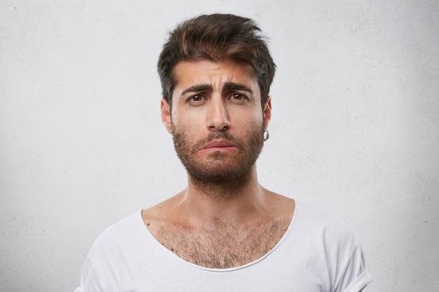 Gestresster bärtiger mann mit traurigem gesichtsausdruck, ohrring und weißem t-shirt, das seine lippe krümmt und traurige neuigkeiten kennt. verwirrter mann. menschen und negative emotionen konzept