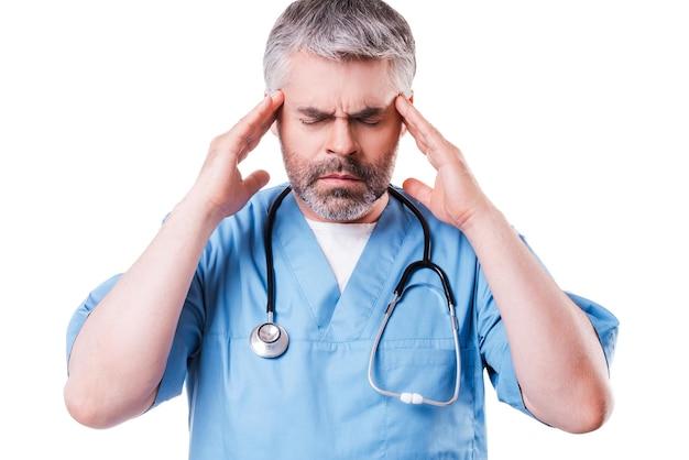 Gestresster chirurg. deprimierter reifer chirurg, der seinen kopf mit den händen berührt und die augen geschlossen hält, während er isoliert auf weiß steht