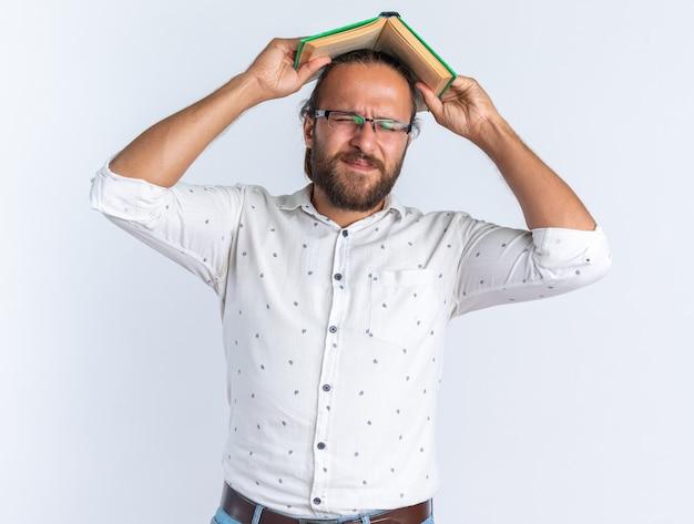 Gestresster erwachsener gutaussehender mann mit brille, der ein offenes buch auf dem kopf mit geschlossenen augen hält, isoliert auf weißer wand