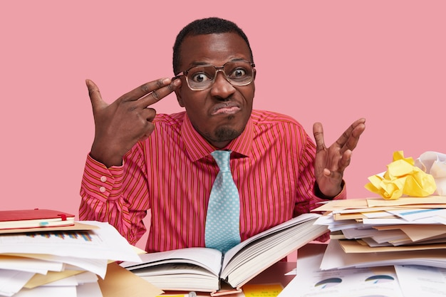 Gestresster frustrierter mann zeigt mit der fingerpistole auf den kopf, macht eine selbstmordgeste, fühlt sich erschöpft und arbeitsmüde, liest wissenschaftliche literatur