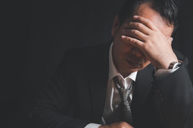 Gestresster geschäftsmann, der problemfinanzkrise und geschäftsinsolvenz auf schwarzem hintergrund hat