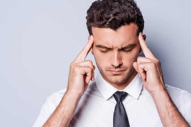 Gestresster geschäftsmann. frustrierter junger mann in hemd und krawatte, der den kopf mit den fingern berührt und die augen geschlossen hält, während er vor grauem hintergrund steht