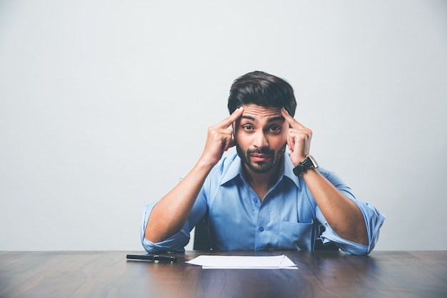 Gestresster indischer geschäftsmann, der kopfschmerzen oder migräneschmerzen hat, während er am bürotisch arbeitet
