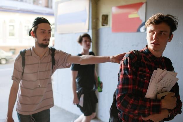 Gestresster intelligenter geek, der versucht, vor straßengang-schlägern zu fliehen. teenager-mobbing. aggressionskonzept