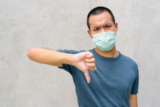 Gestresster junger asiatischer mann, der daumen unten mit maske zum schutz vor coronavirus-ausbruch im freien gibt