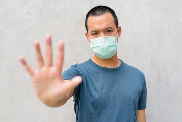 Gestresster junger asiatischer mann, der stoppgeste mit maske zum schutz vor coronavirus-ausbruch im freien zeigt