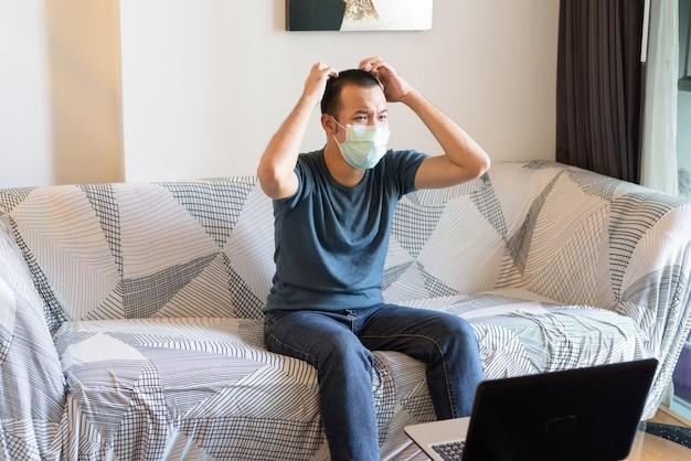 Gestresster junger asiatischer mann mit maske, die fernsieht und zu hause unter quarantäne frustriert schaut