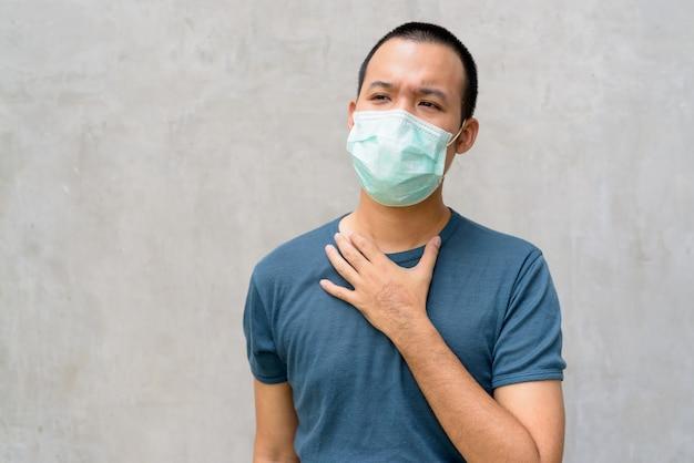 Gestresster junger asiatischer mann mit maske, die krank wird und halsschmerzen im freien hat