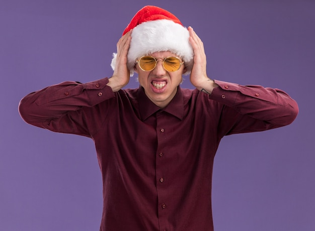 Gestresster junger blonder mann, der weihnachtsmütze und brille trägt, die hände auf kopf mit fest geschlossenen augen halten, die auf lila wand isoliert werden