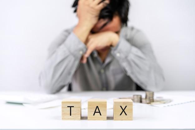 Gestresster junger geschäftsmann, der einkommen, monatliche hausausgaben und steuern berechnet und berücksichtigt