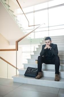 Gestresster junger geschäftsmann im schwarzen anzug, der auf treppe mit kaffeetasse und aktentasche sitzt und verwirrt kopf auf hände lehnt