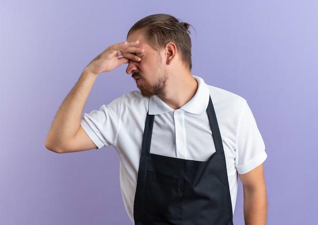 Gestresster junger hübscher friseur, der uniform trägt, die hände auf augen mit geschlossenen augen lokalisiert auf purpurroter wand setzt