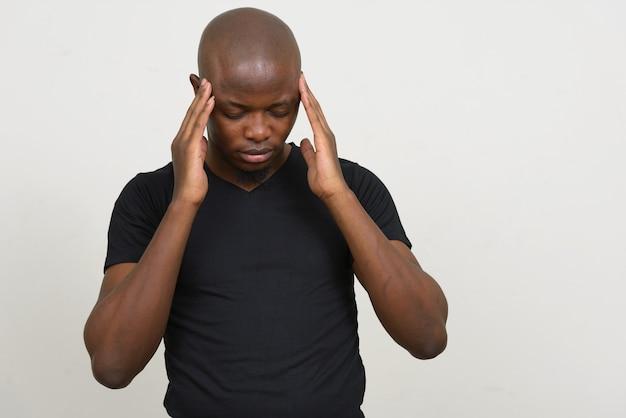 Gestresster junger kahler afrikanischer mann, der kopfschmerzen hat
