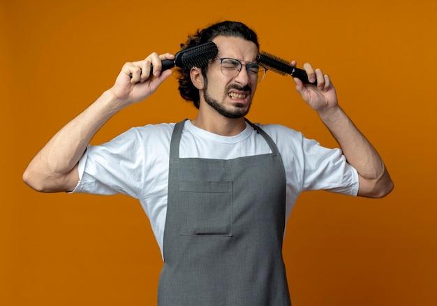 Gestresster junger kaukasischer männlicher friseur, der brille und welliges haarband in einheitlichen berührenden schläfen mit kämmen mit geschlossenen augen trägt, die auf orange hintergrund lokalisiert werden
