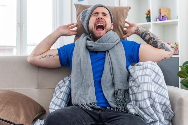 Gestresster junger kranker mann mit schal und wintermütze, der auf dem sofa im wohnzimmer sitzt und ein kissen hinter seinem kopf hält und mit geschlossenen augen schreit