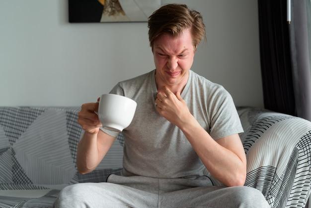 Gestresster junger mann, der kaffee trinkt und zu hause angewidert aussieht