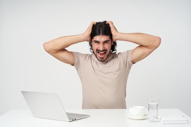 Gestresster kerl, kämpfender geschäftsmann mit schwarzen haaren und bart. bürokonzept. am arbeitsplatz sitzen. hält seinen kopf und schreit vor wut. isoliert über weiße wand