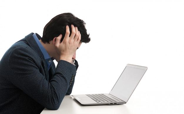 Gestresster mann, der seinen laptop mit dem kopf in den händen betrachtet