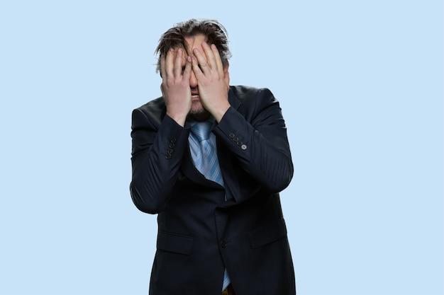 Gestresster mann im anzug, der sein gesicht mit beiden händen berührt. verlust- und ausfallkonzept. auf blauem hintergrund isoliert.