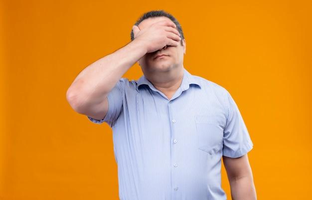 Gestresster mann mittleren alters im blau gestreiften hemd, das augen mit händen auf einem orangefarbenen hintergrund bedeckt