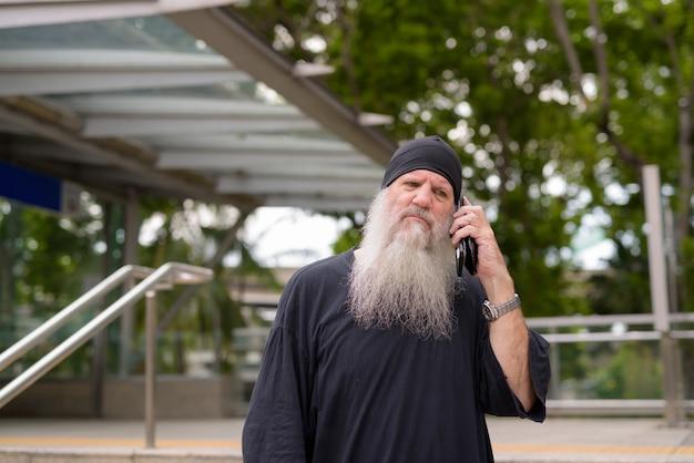 Gestresster reifer bärtiger hipster-mann, der außerhalb des u-bahn-bahnhofs am telefon spricht
