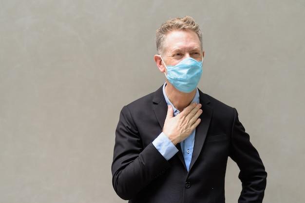 Gestresster reifer geschäftsmann mit maske, die draußen krank wird