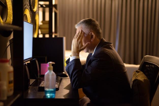 Gestresster reifer japanischer geschäftsmann, der kopfschmerzen hat, während er spät in der nacht überstunden zu hause macht