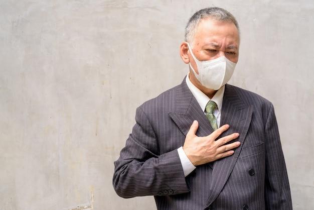 Gestresster reifer japanischer geschäftsmann mit maskenhusten und krank werden im freien