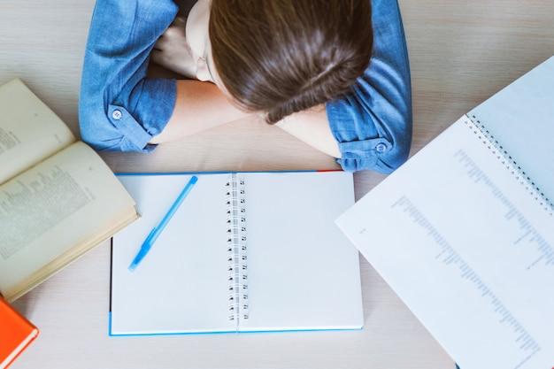 Gestresster student müde vom harten lernen mit büchern in prüfungsvorbereitung vorbereitung, überwältigt high-school-teenager-mädchen erschöpft von schwierigen studien oder zu viel hausaufgaben, cram-konzept