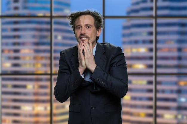 Gestresster und enttäuschter geschäftsmann in einem fernsehstudio. gut aussehender mann im anzug nach nervenzusammenbruch.