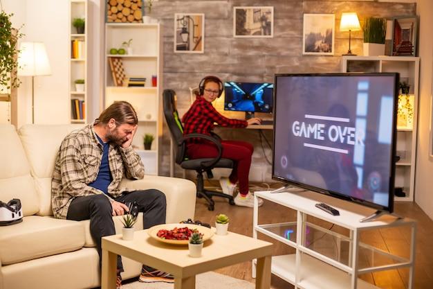 Gestresster und wütender männlicher spieler, der ein spiel verliert, während er spät in der nacht im wohnzimmer spielt