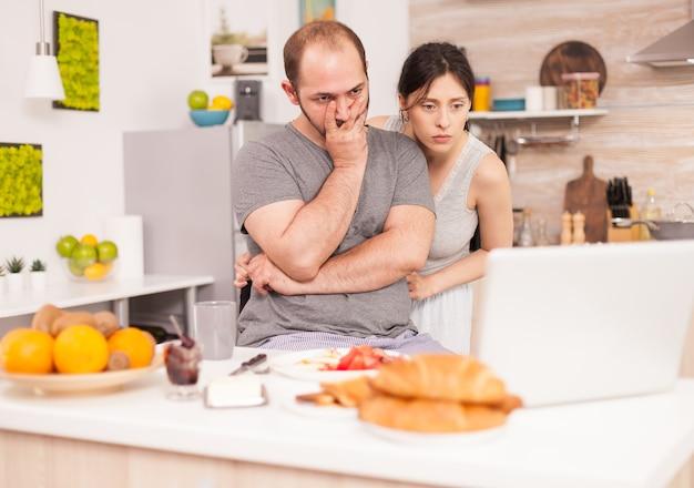 Gestresster unternehmer, der an einem laptop arbeitet, der auf dem küchentisch sitzt, während seine frau das frühstück kocht. unglücklicher, gestresster, frustrierter wütender negativer und verärgerter freiberufler im pyjama, der morgens schreit