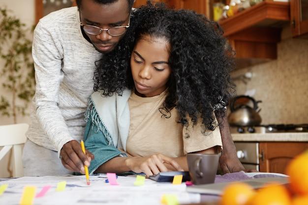 Gestresstes afrikanisches paar, das viele schulden hat und zu hause papierkram erledigt. ernsthafter mann in der brille unter verwendung des bleistifts, der auf ein stück papier auf dem tisch zeigt, während seine junge frau berechnungen auf dem taschenrechner macht