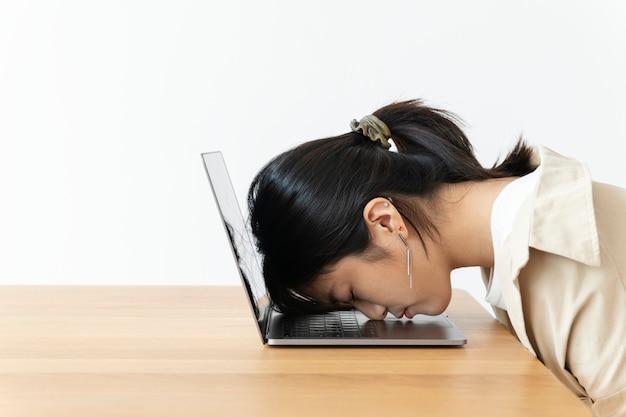 Gestresstes asiatisches mädchen, das ihren kopf auf einem laptop ruht
