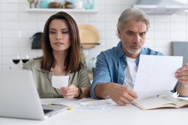 Gestresstes familienpaar, das von hohen stromrechnungen, geldverlust enttäuscht ist. der unglückliche, nervöse ehepartner erhielt eine benachrichtigung über eine hypothek und überprüfte die finanzdokumente.