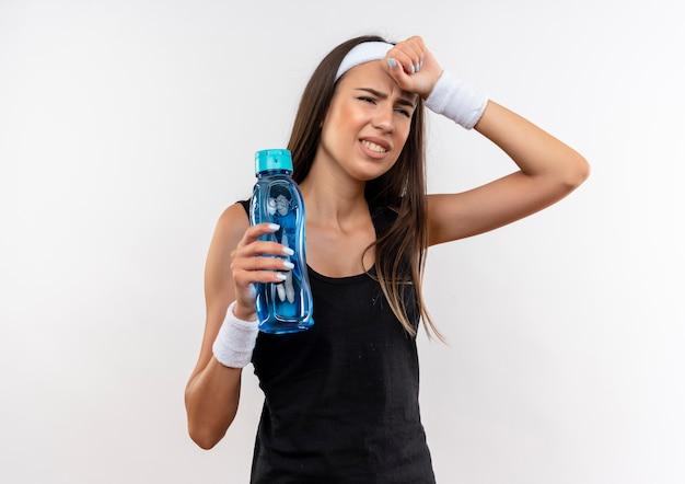 Gestresstes hübsches sportliches mädchen, das stirnband und armband hält wasserflasche mit hand auf kopf lokalisiert auf weißem raum trägt