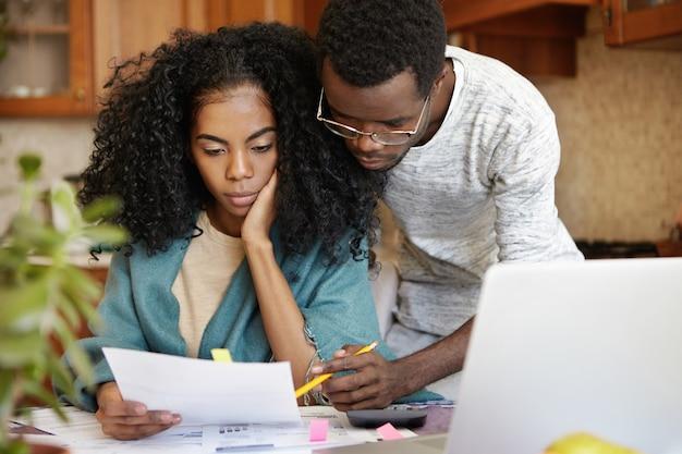 Gestresstes junges afroamerikanisches paar, das gemeinsam papierkram erledigt