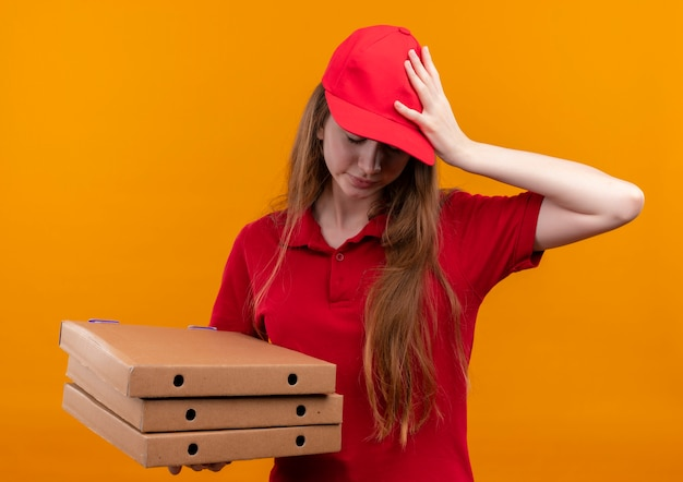Gestresstes junges liefermädchen in der roten uniform, die pakete mit hand auf kopf mit geschlossenen augen auf isolierter orange wand hält