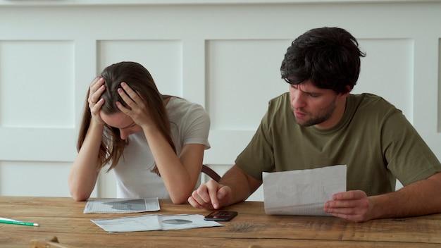Gestresstes junges paar, das monatliche hauskosten berechnet, kreditkartenrechnungszahlung.