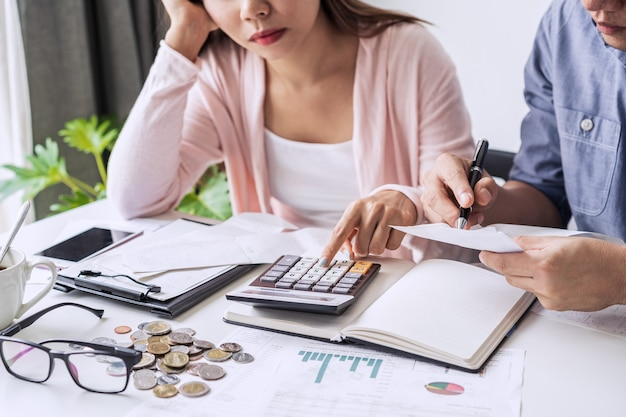 Gestresstes junges paar, das monatliche hauskosten, steuern, bankguthaben und zahlung von kreditkartenrechnungen berechnet