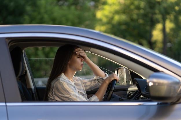 Gestresstes mädchen mit kopfschmerzen fährt auto frustriert unzufriedene junge fahrerin leidet an krankheit