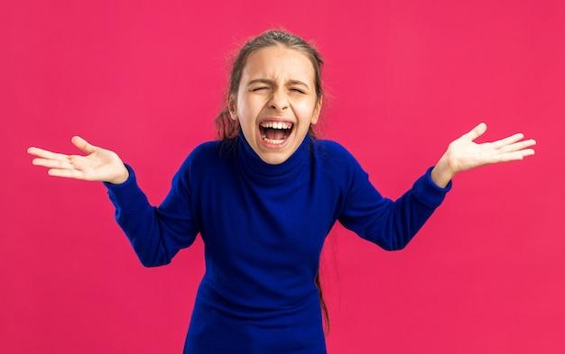 Gestresstes teenager-mädchen, das leere hände zeigt, die mit geschlossenen augen schreien, isoliert auf rosa wand