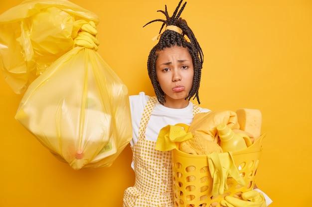 Gestresstes unglückliches afroamerikanisches dienstmädchen sieht überarbeitet aus und trägt müllsack